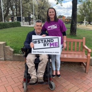Glenn Cairns with Eveleen May from Disability Advocacy NSW, holding a Stand By Me sign